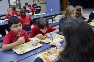 Jude Cobler, left, eats lunch with classmates at All Saints Catholic School in Far North Dallas. Photo/Christina Ulsh