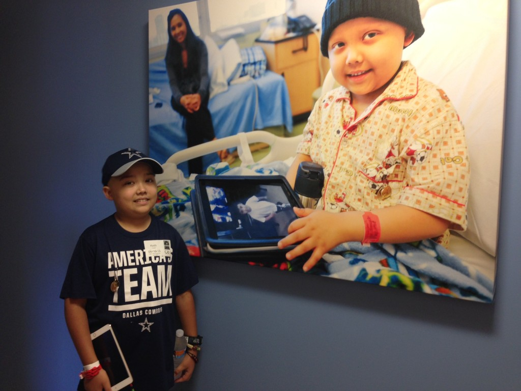 Jude Cobler stands next to a picture of him hanging on a wall at Children's Medical Center in Dallas. Jude's Acute Lymphoblastic Leukemia has relapsed. Photo/Lauren Silverman
