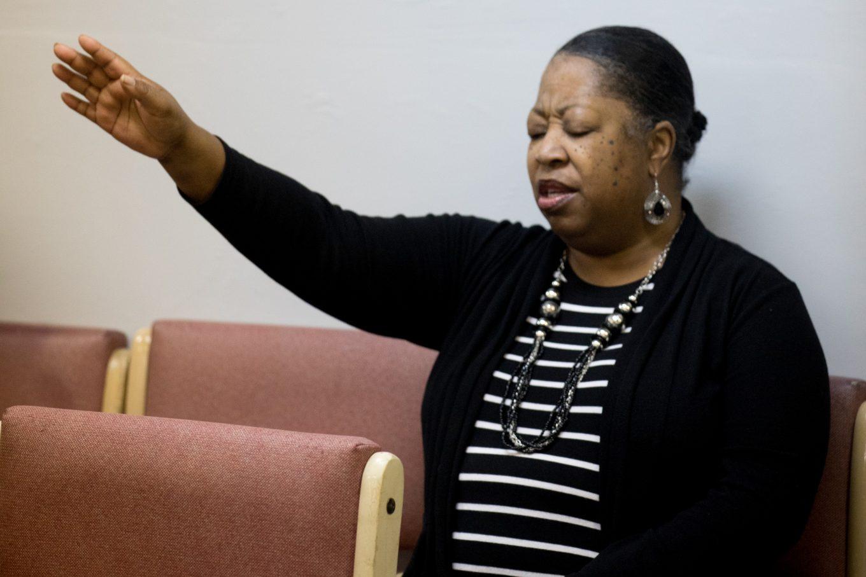 Debbie Spruell with hand raised in prayer at church