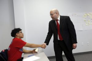 Kimball High School Academy of Hospitality and Tourism student Francisco Gamez (left) practices his handshake with Talent Development Facilitator Wes Esquivel while on a field trip to Workforce Solutions Greater Dallas. Photographed in Dallas, Texas on Friday, February 17, 2017. (photo © Lara Solt)
