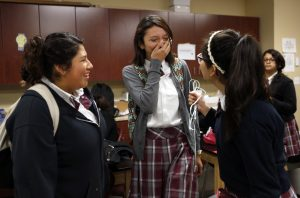 Alex Gutierrez, center, jokes with students Andrea Martinez, left, and Marisol Mendiola, right, at the start of physics class at International Leadership of Texas Garland High School. Photo/Lara Solt