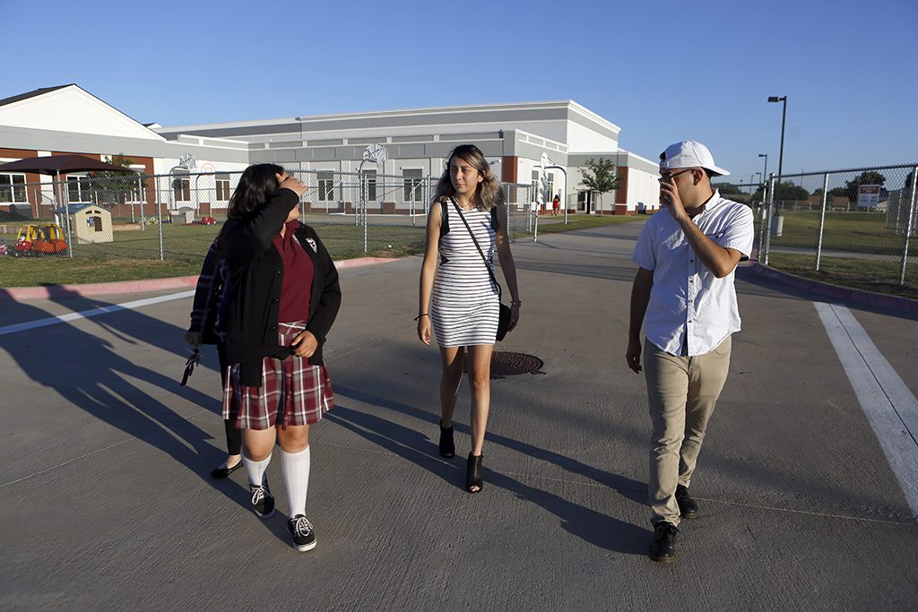 Alexandria Gutierrez (center), Anthony Banuelos (right) and Rebecca Banuelos (left) walk out to their cars after the senior banquet at International Leadership of Texas in Garland on Wednesday, May 25, 2017. (photo © Lara Solt)