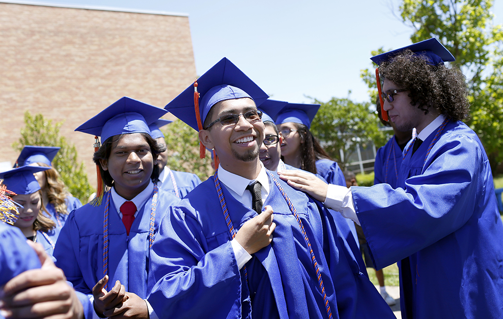 Joel Luera is congratulated by other graduates at W. W. Samuell Early College High School in Dallas. Photo/Lara Solt