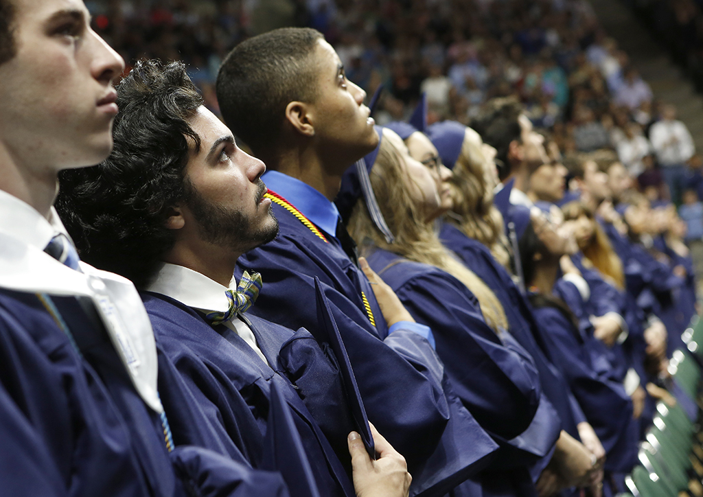 Ricky Rijos Jr. (second from left) and other graduates during the National Anthem at graduation from Flower Mound High School at UNT Coliseum in Denton, on Monday, June 6, 2017. (photo © Lara Solt)