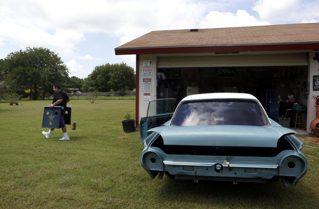 Rene Munguia works to restore a 62 Ford Thunderbird for a friend at his home in Ovilla, Texas on Saturday, August 27, 2016. (photo © Lara Solt)