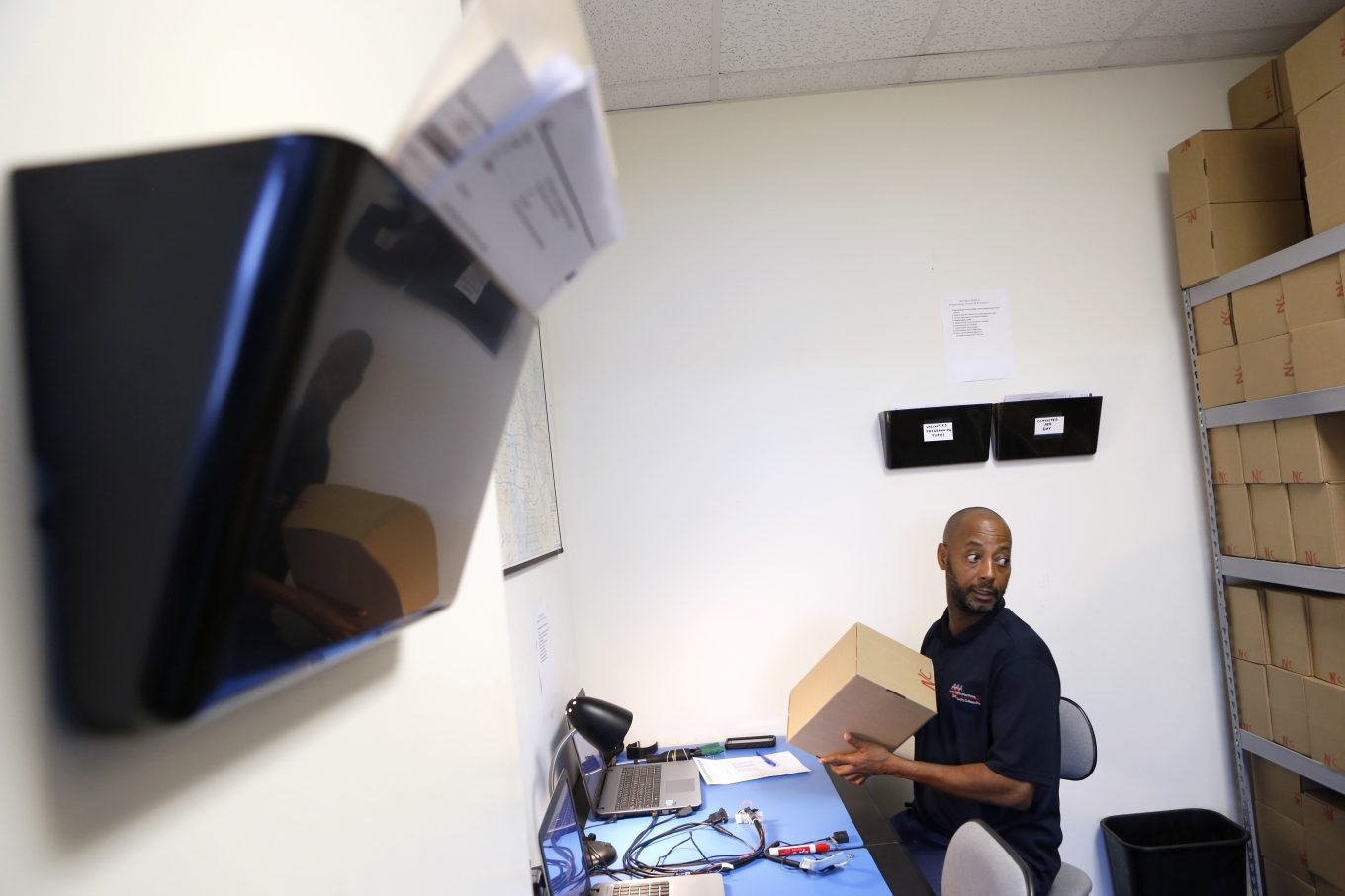 Programmer Angelo Collins works on transit validators for DART at AAA Data Communications Inc. in Dallas. Photo/Lara Solt