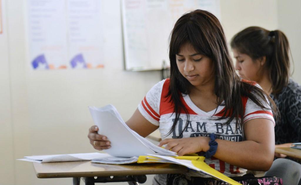 Dilcia Mazariegos organizes paperwork in an ESL class. Photo/Christina Ulsh