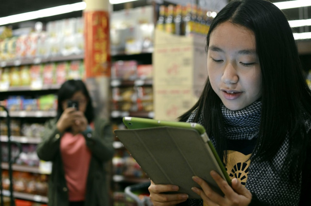 From left: Niuying Cao records classmate Jiaying Zhang reciting a poem on her iPad to a customer at 99 Ranch Market -- the assignment is designed to help students practice their English. Photo/Christina Ulsh