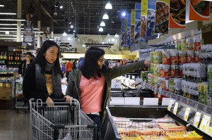From left: Jiaying Zhang and Niuying Cao go shopping at 99 Ranch Market in Plano to stock up on treats and drinks that remind them of home. Photo/Christina Ulsh