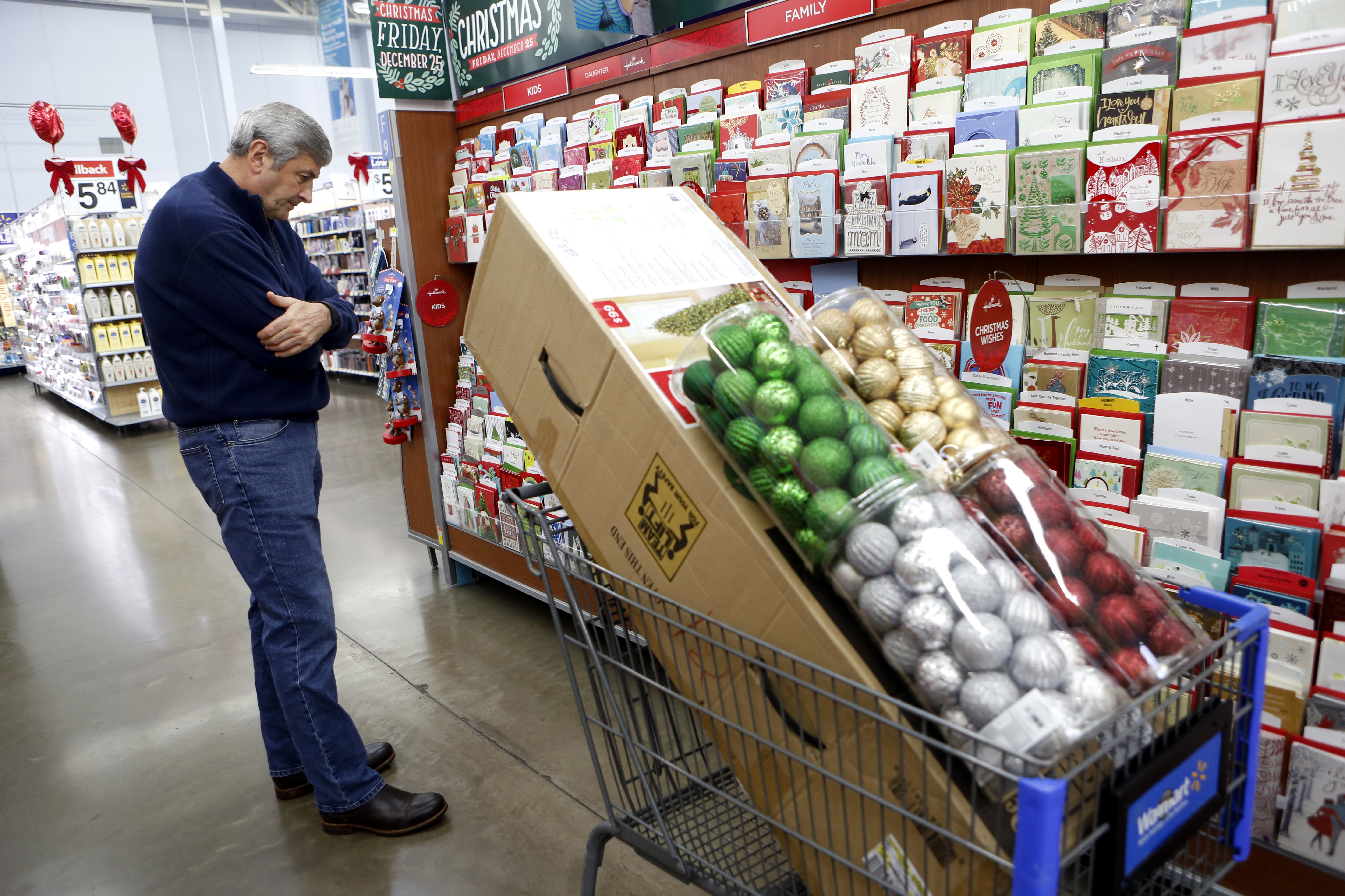 Bob Roe looks for Christmas cards after selecting a Christmas tree and ornaments while shopping at Walmart in Dallas. Photo/Lara Solt