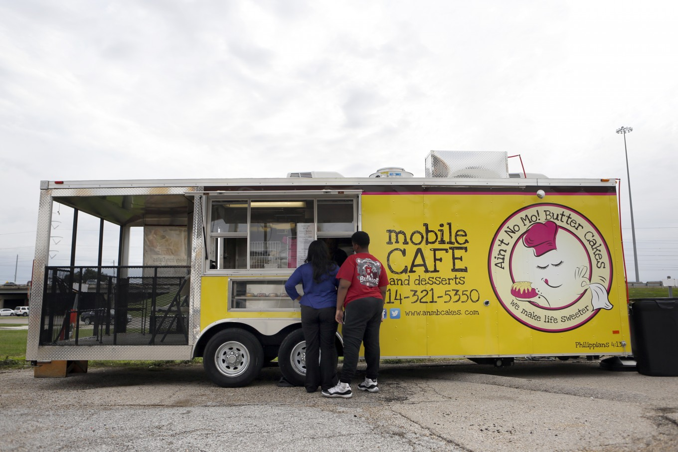 Customers Tara Hairston and son Tyler Kennedy, 14, order lunch at Quincy and Sheri Brown's food truck, Ain't No Mo! Butter Cakes.
