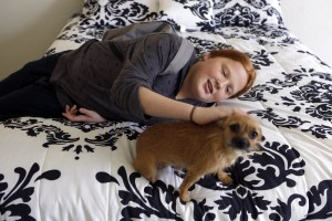 """After three years staying in motels, the Rosenheim family just moved into a three-bedroom home where each child has their own bed. Benjamin (12) pets the family dog, """"Little,"""" in his parents room. (photo copyright Lara Solt)"""