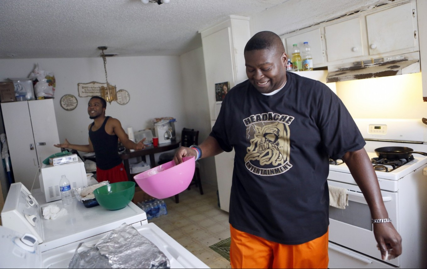 Charles 'CJ' Johnson, right,  jokes with Brandon Jones while making dinner at home. Photo/Lara Solt
