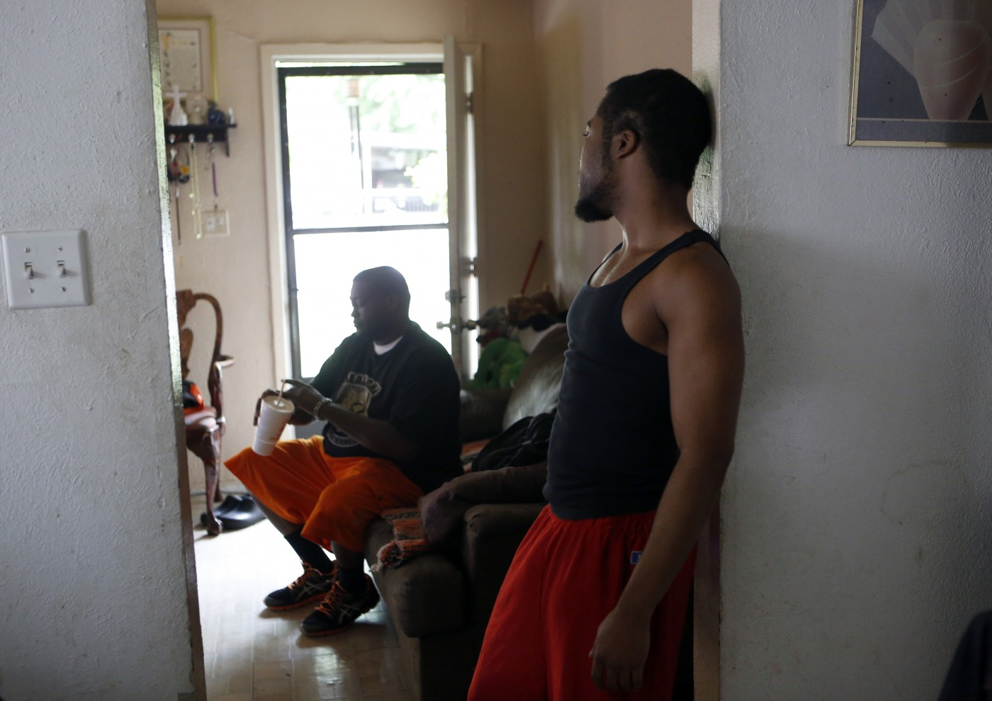 "Charles 'CJ' Johnson, left, and Brandon Jones talk at Johnson's home in Dallas. Jones, who still stops by to get his mail, lived with Johnson for five years. ""That's my dad basically,"" Jones says. ""Everybody calls him 'the godfather.'"" Photo/Lara Solt"