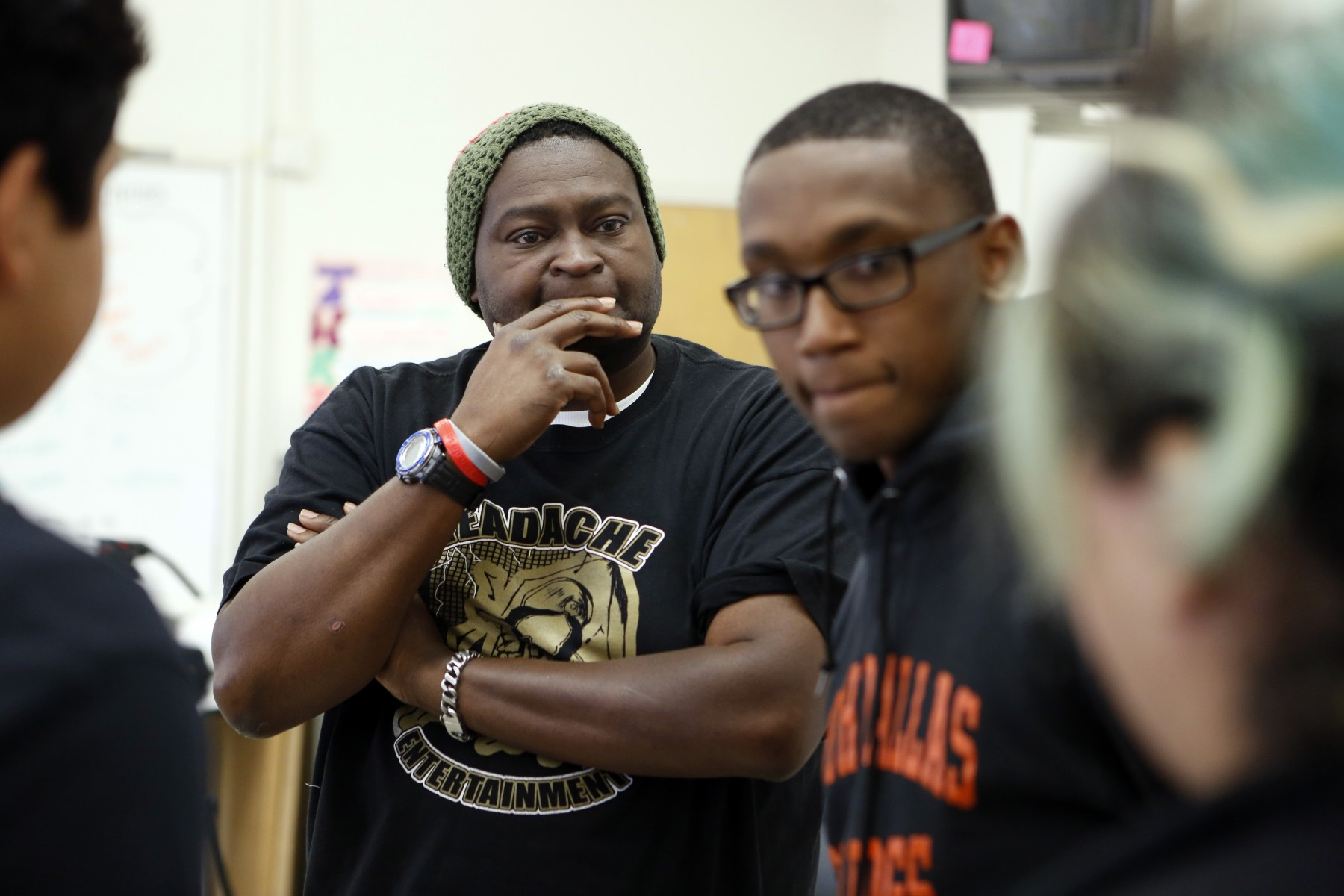 Charles 'CJ' Johnson, left, and Desmond Davis, a student who is currently living with him, talk to other Action Team volunteers during an Action Team meeting at North Dallas High School. Photo/Lara Solt
