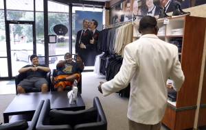 Charles 'CJ' Johnson, left, helps Desmond Davis with his collar while trying on a tux for his prom at Al's Formal Wear in Dallas. Photo/Lara Solt