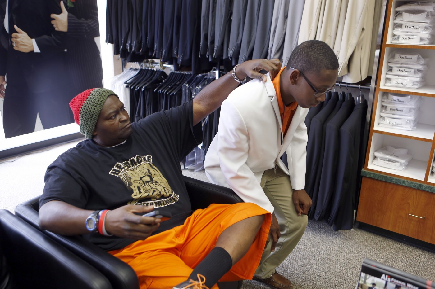 Charles 'CJ' Johnson, left, helps Desmond Davis with his buttons while trying on a tux for his prom at Al's Formal Wear in Dallas. Photo/Lara Solt