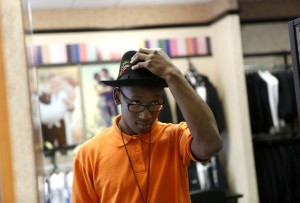 North Dallas High School student Desmond Davis tries on a hat while looking for a tux for his upcoming prom at Al's Formal Wear in Dallas. Photo/Lara Solt