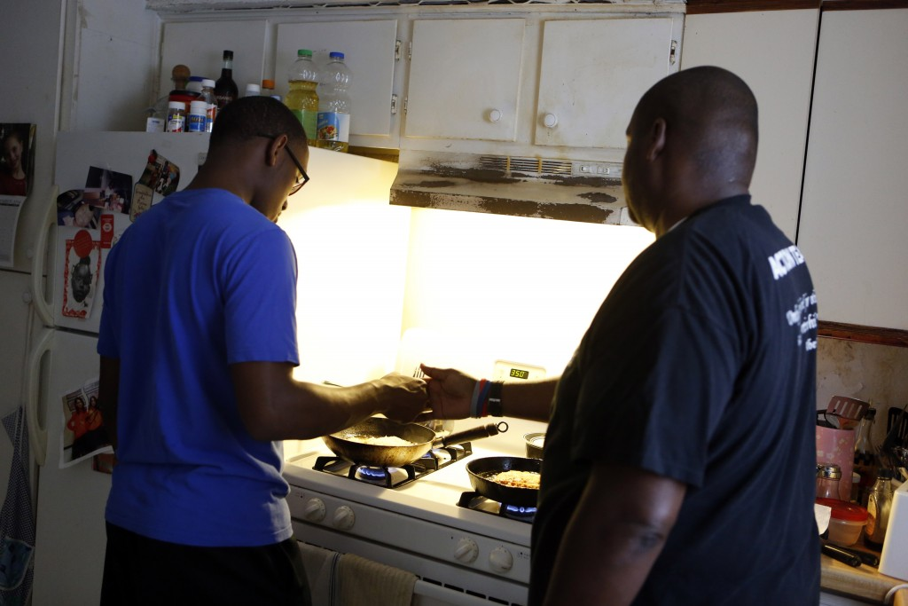 Charles 'CJ' Johnson, right, instructs Desmond Davis on how to prepare chicken fried chicken at his home in Dallas. Johnson has taken in more than 40 homeless boys since 2001. Photo/Lara Solt