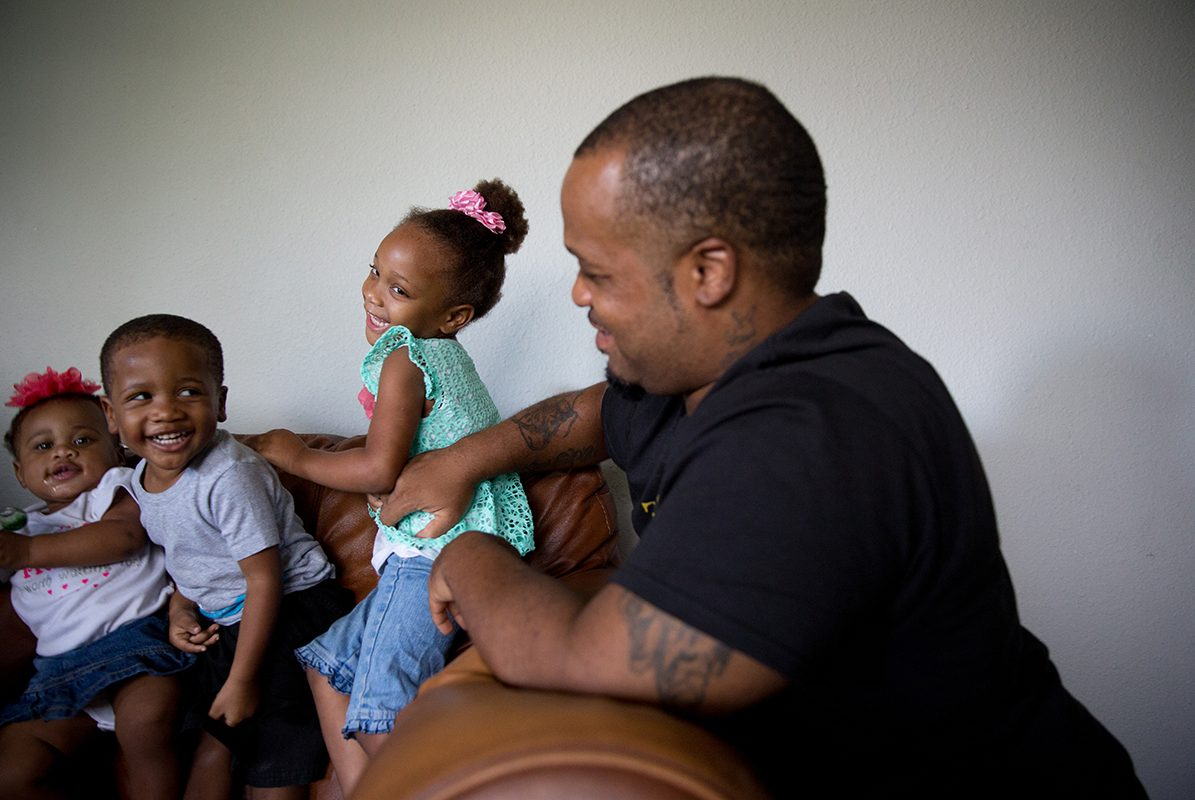 Stanley Walington tickles his daughter Promiss, 3, in their apartment in Fort Worth.