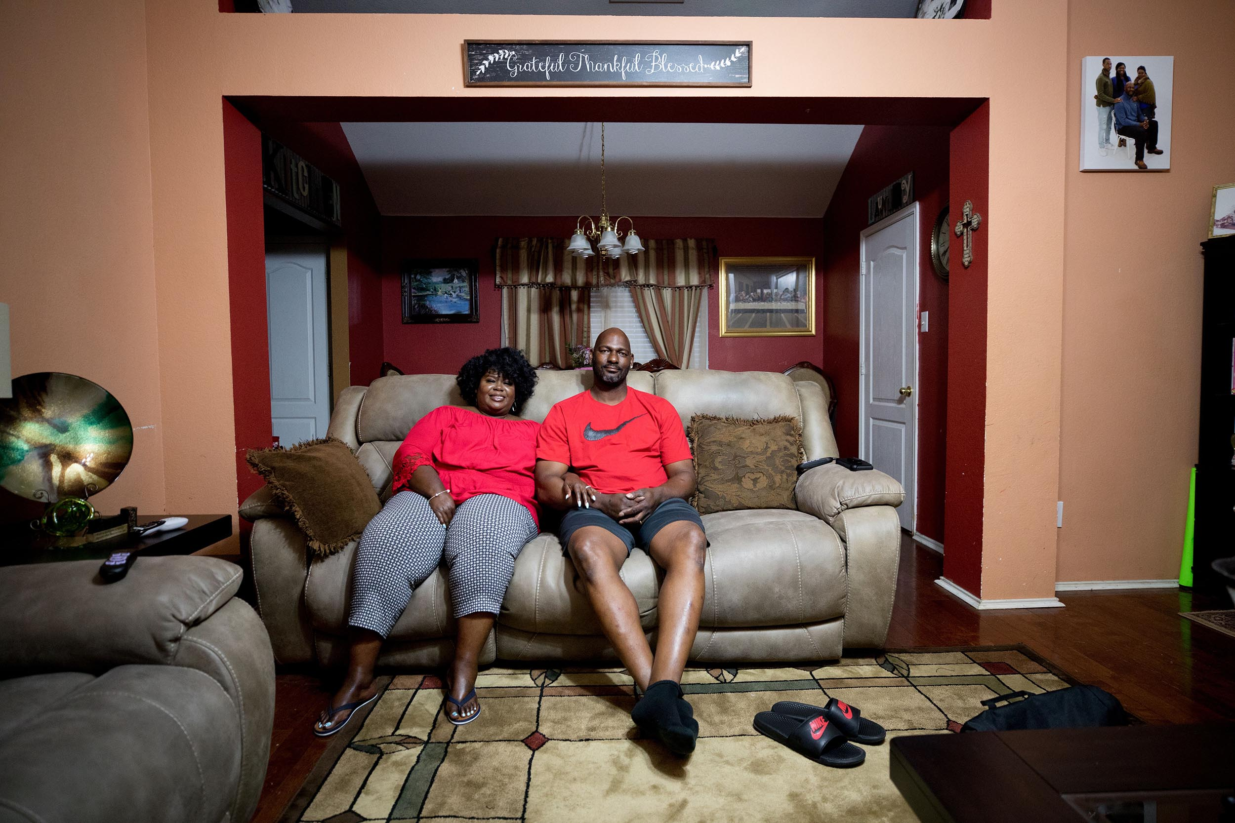Kim and Ed sit on a couch together at home. Photo: Allison V. Smith for KERA
