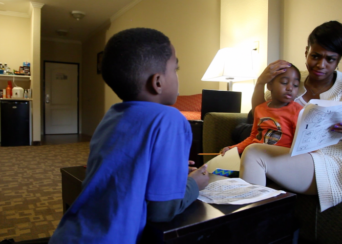 Jenn and her sons, Jayden and Jordan working on homework in their motel room. Photo/Thorne Anderson