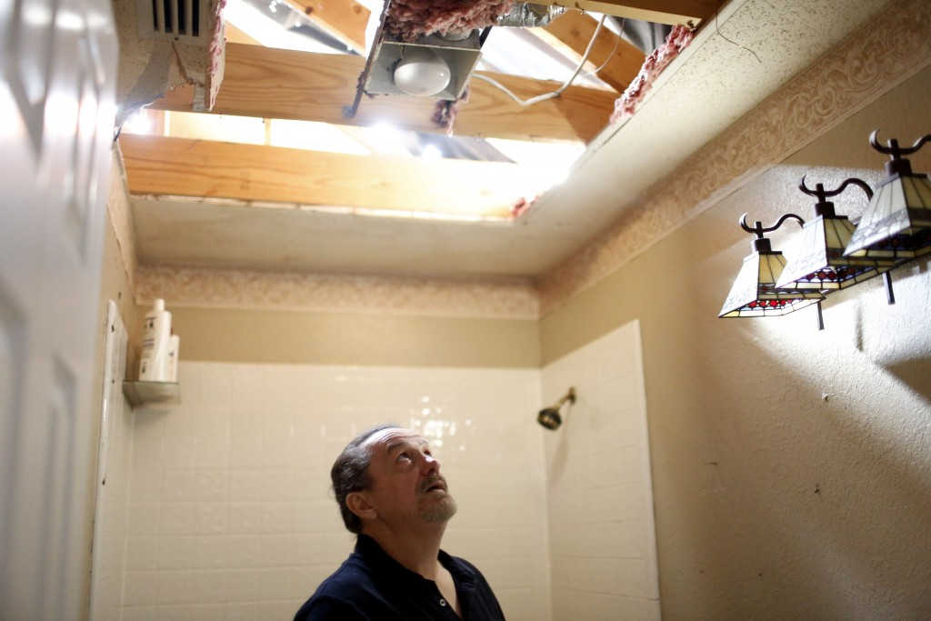 Anthony Fowler-Rainone, of Rowlett, looks into a hole in the bathroom ceiling that caved in when his home was seriously damaged in the December tornadoes. Photographed Monday, February 1, 2016. (photo copyright Lara Solt)