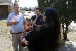 Lindsay Diaz holds her son, 7-month-old Arian Krasniqui, while speaking with Stephen Miller of Lone Star Remodeling (left) and Joel Weimer of The Next Project Company about how to proceed with rebuilding their home. Photographed Friday, February 19, 2016. (photo copyright Lara Solt)