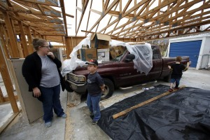 Jessica Cadick, and two of her children (from left) Joshua Tucker, 9, and Kaden Beck, 6, at their Garland home where they have already started rebuilding after their house was seriously damaged in the December tornadoes. Charles is a general contractor and lost his truck, which means he canÕt work. But since the landlord is rebuilding the damaged rental house, Charlie will be on that rebuilding team, which is a paying job. Photographed Sunday, February 21, 2016. (photo copyright Lara Solt)
