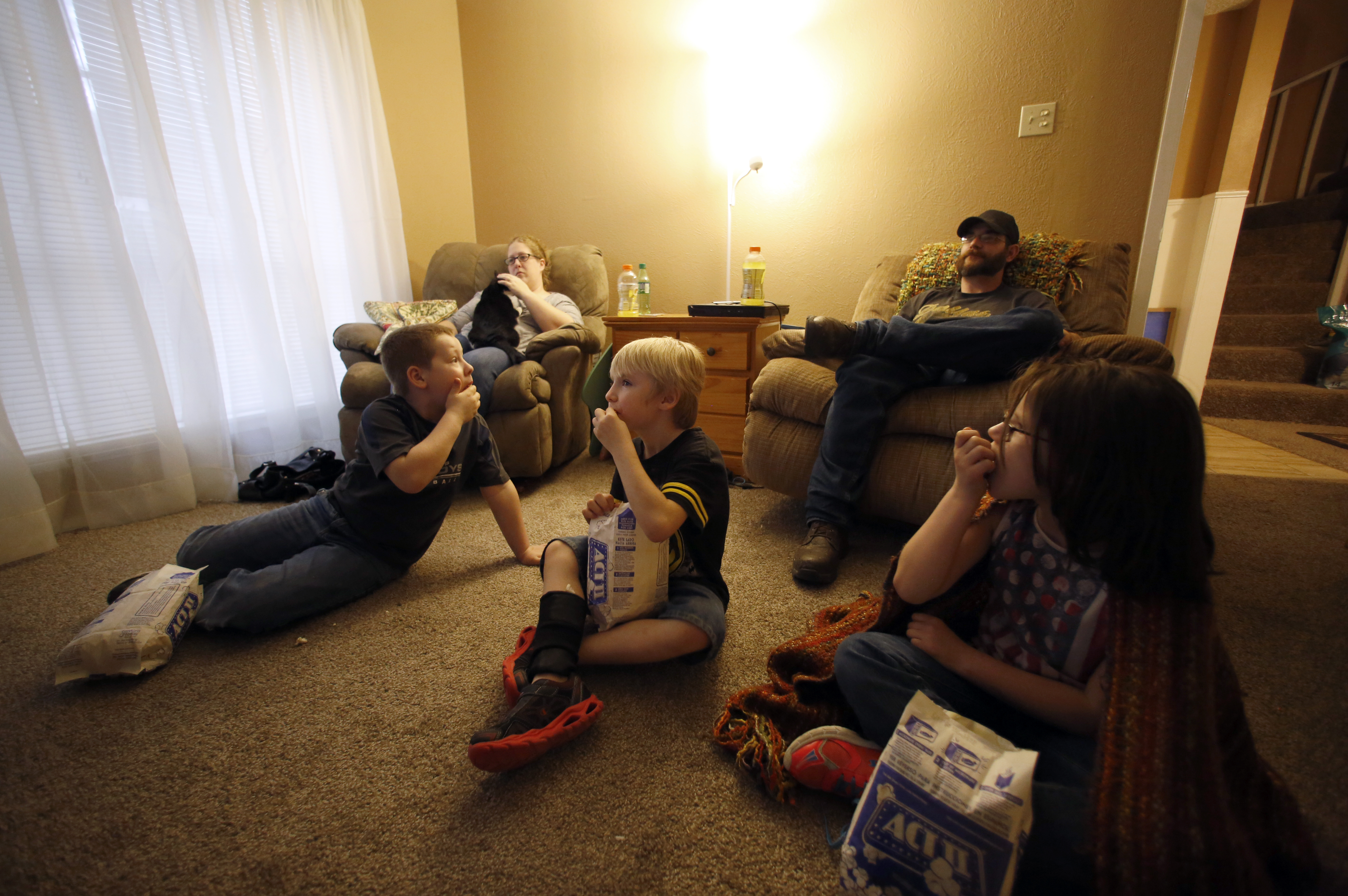 Jessica Cadick, her fiancé Charlie Beck, and their children, from left, Joshua Tucker, 9, Kaden Beck, 6, and Kairi Beck, 8, continue their tradition of family movie night at their rental house in Garland. Photo/Lara Solt