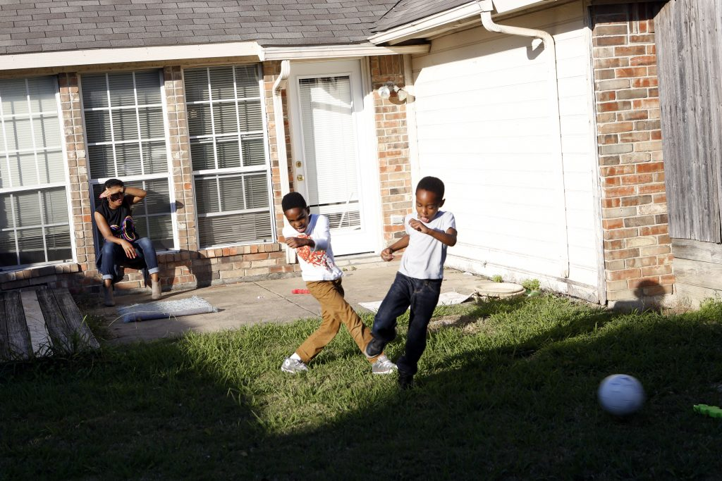 Jennifer Anderson watches her sons Jayden Anderson, 6, (left) and Jordan Anderson, 5, (right) play in the backyard after school at their rented home they share with a roommate in Garland. Their apartment was destroyed in a tornado in December 2015. Photographed on Monday, November 15, 2016. (photo © Lara Solt)