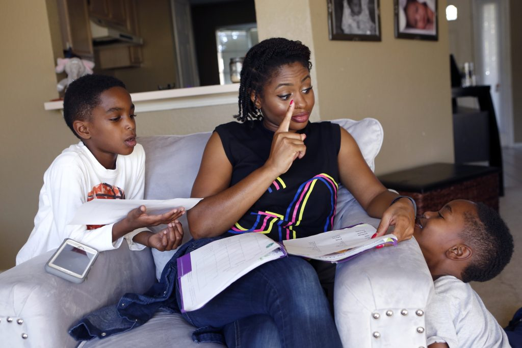 Jennifer Anderson and her sons Jayden Anderson, 6, (left) and Jordan Anderson, 5, (right) go over homework at their rented home they share with a roommate in Garland. Their apartment was destroyed in a tornado in December 2015. Photographed on Monday, November 15, 2016. (photo © Lara Solt)