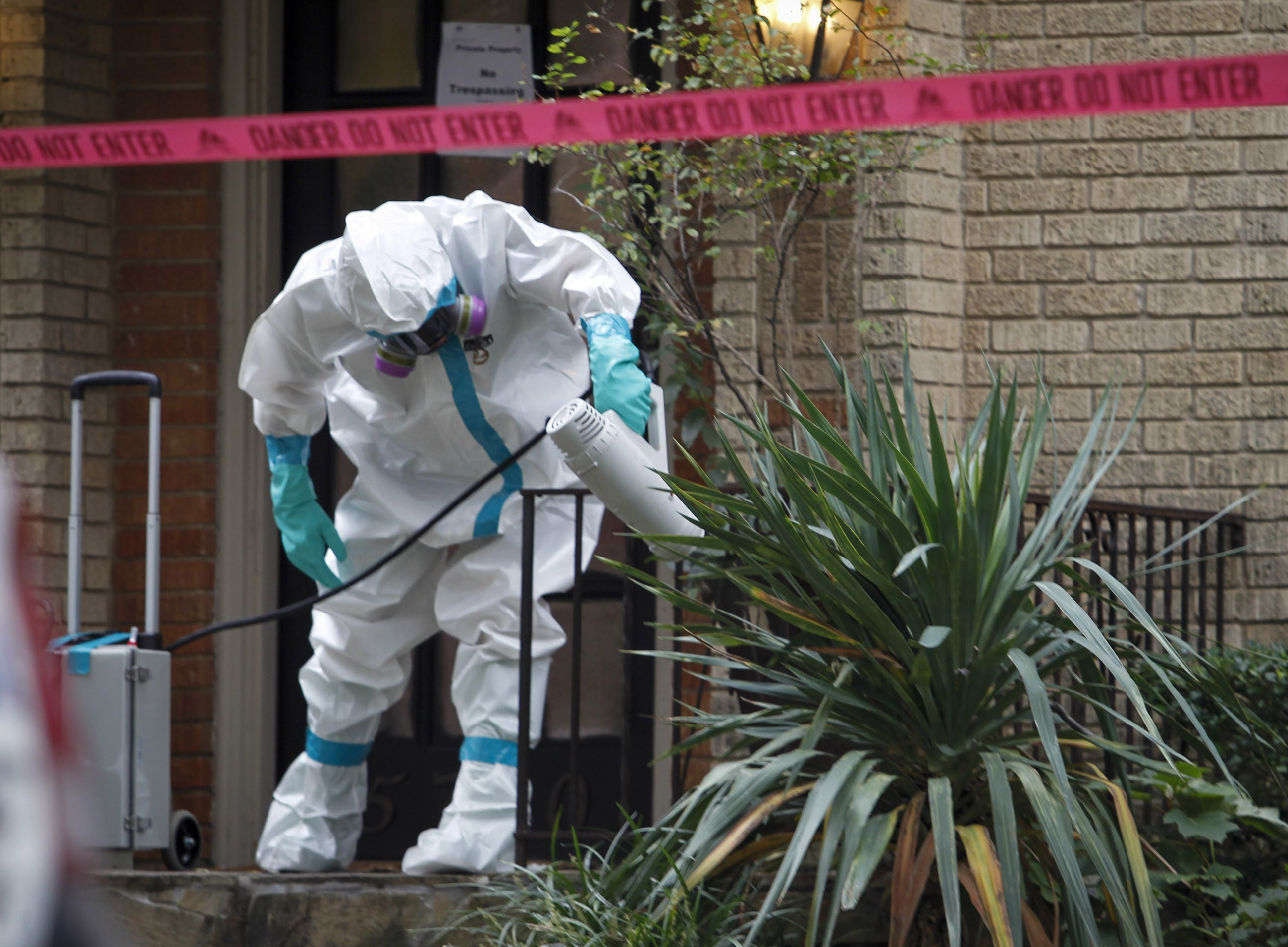 A worker with CG Environmental-Cleaning Guys sprays disinfectant outside the Marquita Street, Dallas apartment building  where a health care worker believed to be infected with Ebola lives on Sunday, Oct. 12, 2014. (Jim Tuttle/The Dallas Morning News)