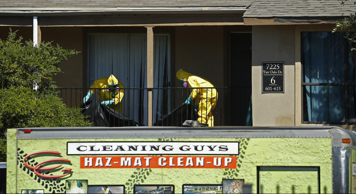 Cleaning Guys Environmental workers prepare to cover the apartment with plastic material in The Ivy Apartment complex  where Ebola victim  Thomas Duncan was staying in Dallas, Oct. 3, 2014 in Dallas. (Nathan Hunsinger/The Dallas Morning News)