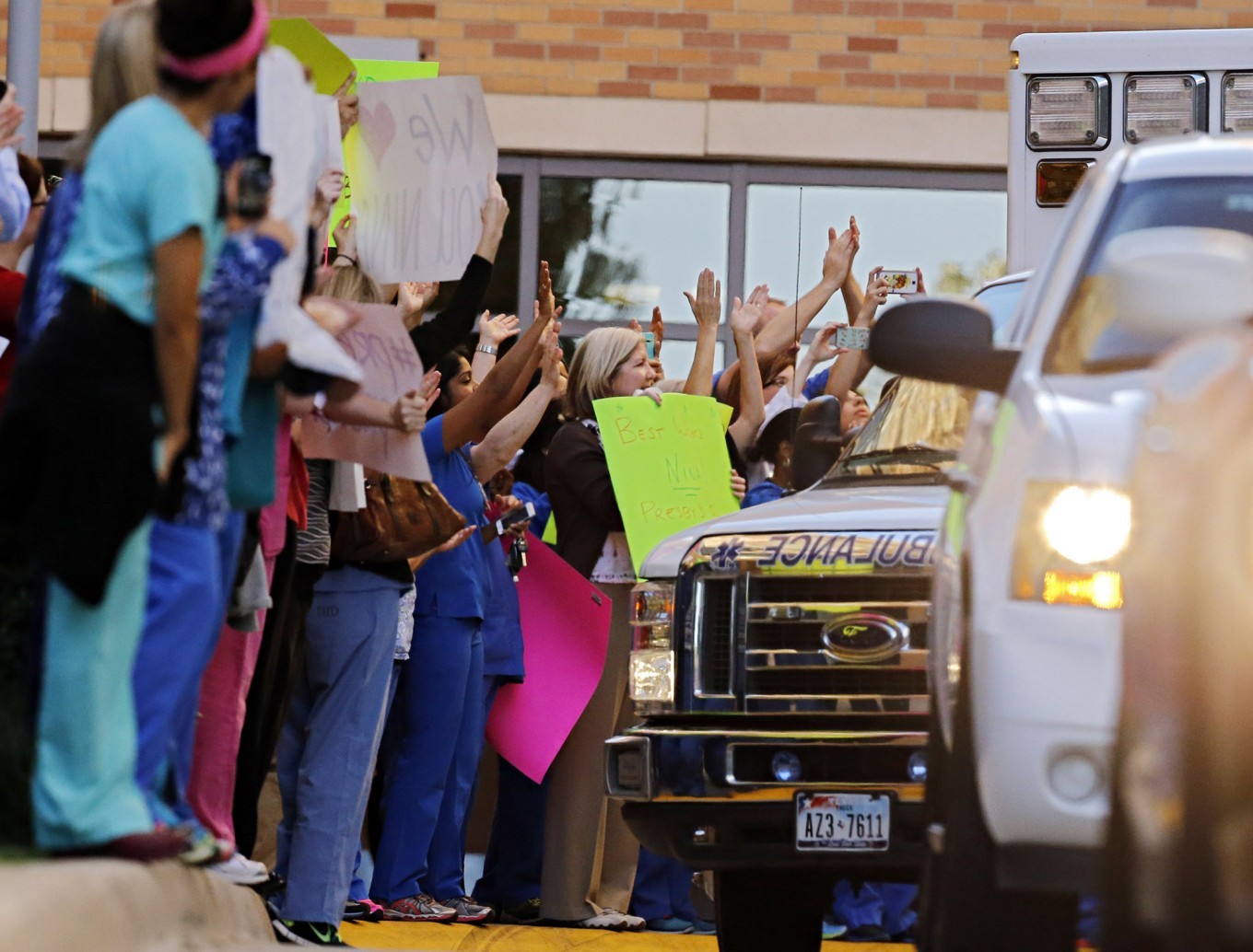 Hospital staff cheer as Nina Pham is driven via ambulance from Texas Health Presbyterian Hospital  to a plane at Dallas Love Field Thursday, October 16, 2014 in Dallas. (G.J. McCarthy/The Dallas Morning News)